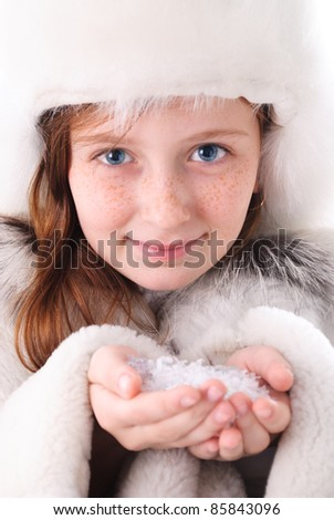 Tinage girl in fur coat and closeup hands with snow - stock photo