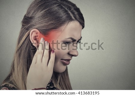Tinnitus. Closeup side profile sick young woman having ear pain touching her painful head temple colored in red isolated on gray background - stock photo