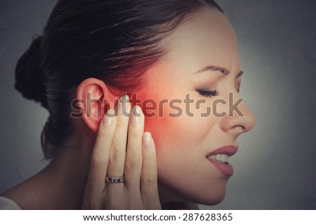 Tinnitus. Closeup up side profile sick female having ear pain touching her painful head isolated on gray wall background  - stock photo