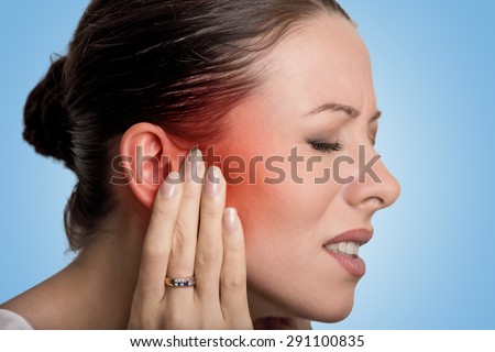 Tinnitus. Closeup up side profile sick female having ear pain touching her painful head isolated on blue background  - stock photo