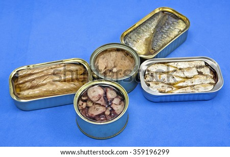 Tins of sardines and mackerel in different sizes open isolated on blue background - stock photo