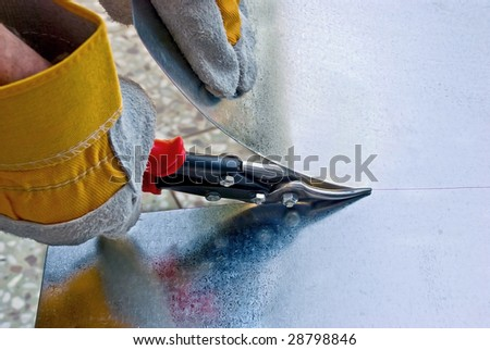 Tinsmith cuts a sheet metal by snips - stock photo