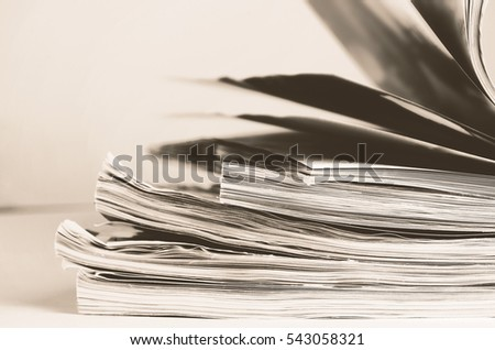 tinted image stack of magazines to turn pages horizontal