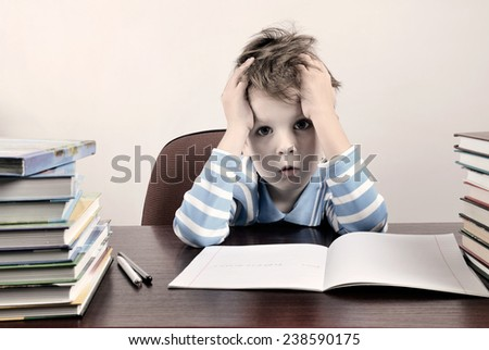 tinted image tired boy sitting at a desk and holding hands to head horizontal - stock photo