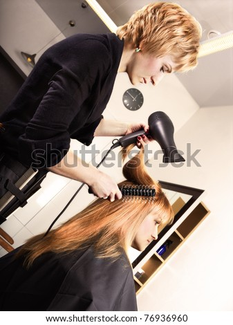 Tinted portrait of hairstylist at work - stock photo
