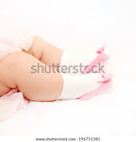 Tiny baby feet in pink shoes of newborn princess on a white bed - stock photo