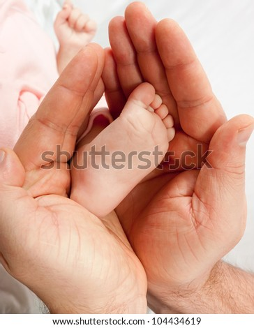 Tiny baby foot in a Father's big hands.