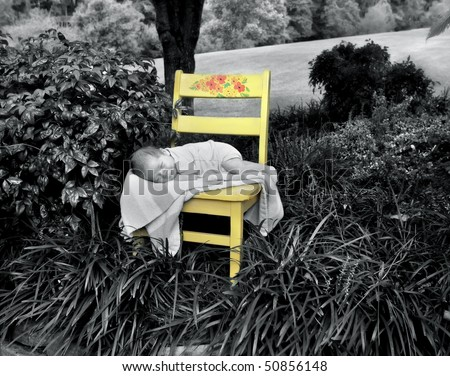Tiny baby lays on a striped blanket on a yellow, wooden chair.  Chair sits surrounded by trees and lush foliage. - stock photo