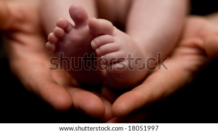 Tiny baby's feet in her father's hands - stock photo