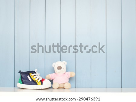 Tiny baby shoes and teddy bear on the table in baby's room - stock photo