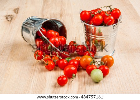 Tiny baby tomatoes in a small bucket on a wooden table. Vertical shot, copy space