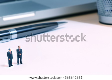 Tiny Business dolls on blank page - stock photo