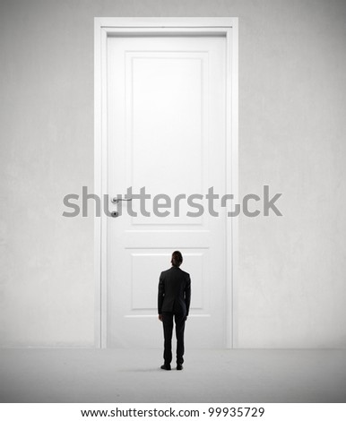 Tiny businessman standing in front of a giant door - stock photo