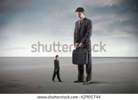 Tiny businessman standing in front of a giant one - stock photo