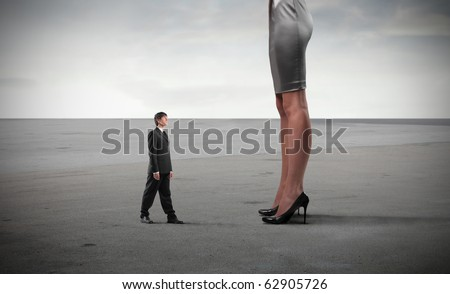 Tiny businessman standing in front of huge woman's legs - stock photo