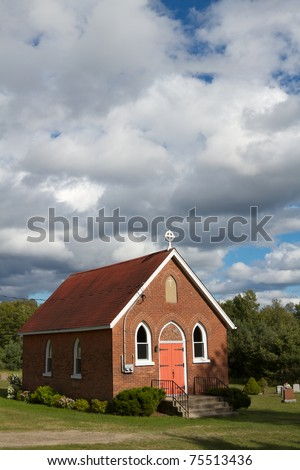 Tiny Church - Small brick church on a green field with blue skies and clouds.