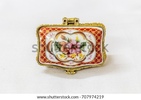 Tiny colorful jewel box with gold platted crimp in a white background. Macro with extremely shallow depth of field. Selective focus on the jewel box.
