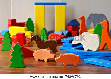 Tiny colorful wooden toy shapes and building blocks on hardwood floor.  Macro with extremely shallow dof.  Selective focus on toys in foreground. - stock photo