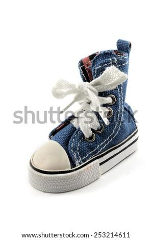 tiny denim shoe on a white background - stock photo
