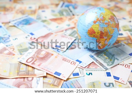 Tiny Earth globe over the surface covered with the multiple bank note bills - stock photo