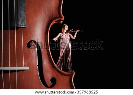 Tiny female violinist playing a violin staying on the edge of the big one over black background - stock photo
