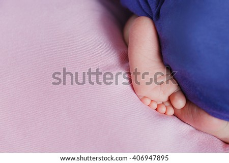 tiny foot of newborn baby. Soft newborn baby feet against a pink blanket. baby feet with toes curled up - stock photo