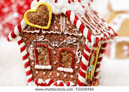 Tiny gingerbread house ornament (made of resin and painted to look like a traditional baked gingerbread house with candy trim).  Macro with extremely shallow dof. - stock photo