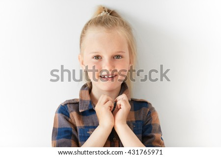Tiny girl with blond pony-tail melting with joy and standing still with arms cupping together. Joyful child opening mouth in surprise waiting for miracle to happen in white room. - stock photo