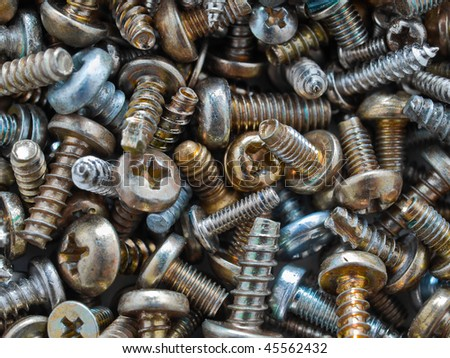 Tiny gold and silver colored screws from electronic components, viewed from above - stock photo