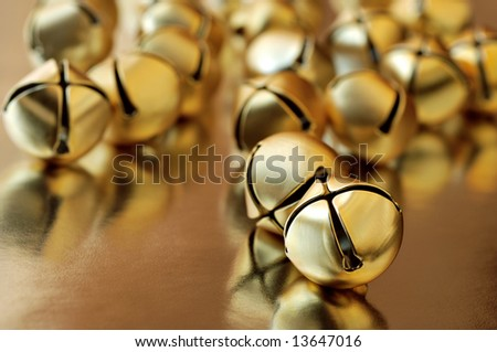 tiny gold jingle bells reflecting on metallic gold paper.  Macro with extremely shallow dof.  Selective focus on closest bell. - stock photo