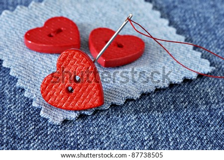 Tiny heart shaped buttons with needle and thread on denim fabric with copy space.  Macro with shallow dof. - stock photo