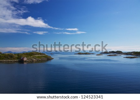 Tiny islands with fishing houses in norwegian sea - stock photo