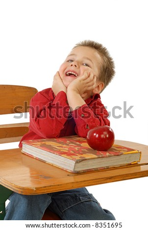 Tiny little student at a desk with textbook and apple - stock photo