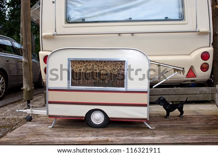 Tiny model caravan for a small pet dog parked at the back of the owners full size caravan in a campsite. - stock photo