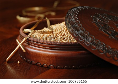 Tiny mustard seeds (symbol of faith) in decorative wooden box with gold cross pendant on wood background.  Macro with shallow dof.  Selective focus on cross with single seed on table. - stock photo