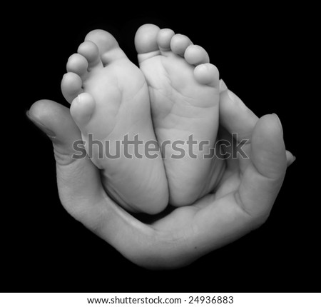 Tiny newborn baby feet in hand
