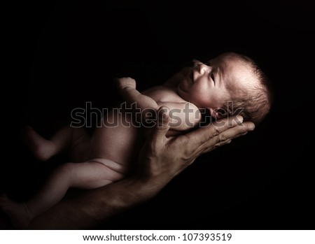 Tiny newborn baby girl on the father's hand. - stock photo