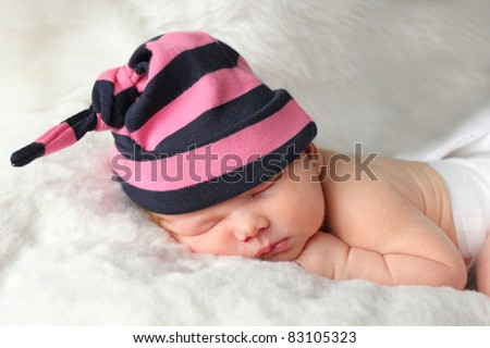 Tiny newborn baby lying on fur blanket asleep