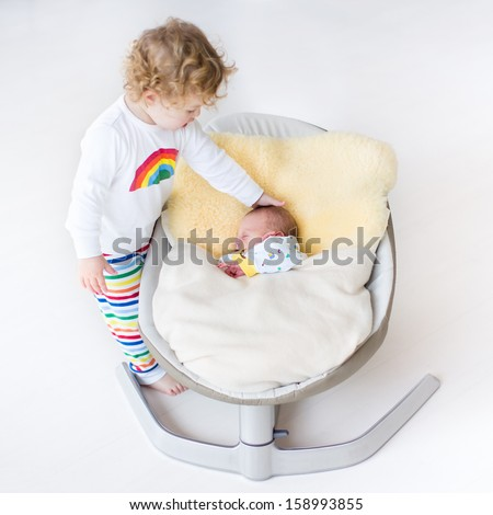 Tiny newborn baby sleeping in a swing on a sheepskin with his toddler sister standing next to him - stock photo
