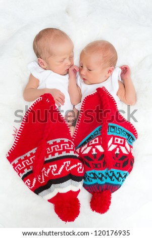 Tiny newborn twins sleeping inside knitted red hats - stock photo