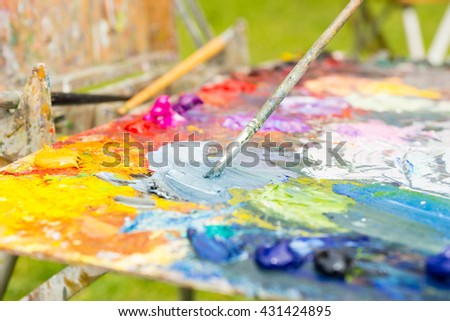 Tiny paintbrush mixing colors on the multicolored palette of blended oil paints outdoors - stock photo