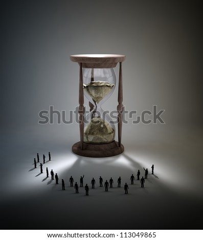 Tiny people standing around an antique hourglass - stock photo