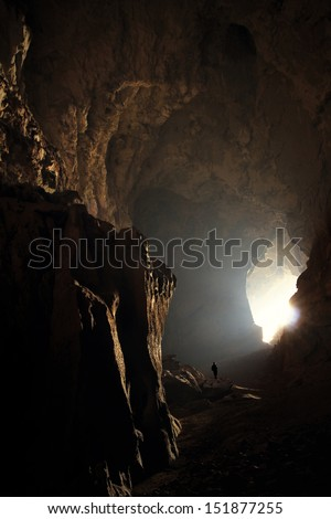 tiny person in huge cave in Laos - stock photo