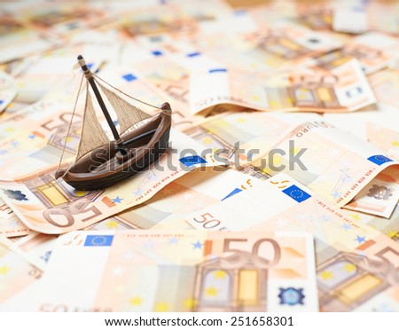 Tiny ship over the surface covered with the multiple fifty euro bank notes - stock photo