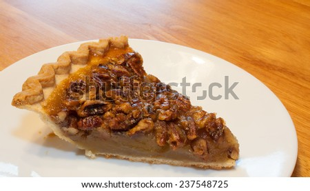 Tiny slice of pecan pie on a white plate - stock photo