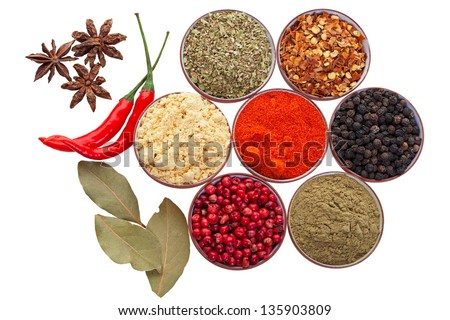 Tiny spices bowls along with loose star anise, bay leaves, & hot red peppers isolated on white.  Includes: oregano, red chilies, whole black pepper, sage, whole red pepper, garlic powder, and paprika.