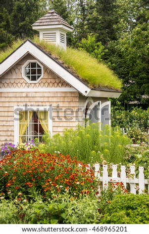 tiny structure with green roof and garden in front, with cat shaped picket fence and trees in the background.