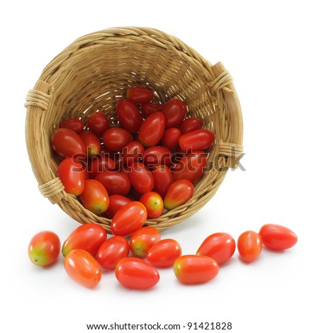 Tiny sweet tomatoes spilled out of the rattan basket isolated on white background. - stock photo