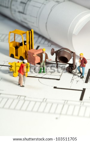 Tiny toy model figures of tradesmen and workers in the construction industry with their equipment on a building site on a blueprint plan for a house design - stock photo