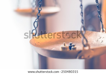 Tiny weights on vintage balance scales - stock photo